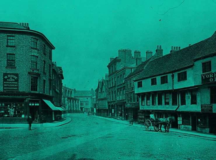 Wide road with buildings either side. A horse and cart are pictured on the right. The image has a green tint.