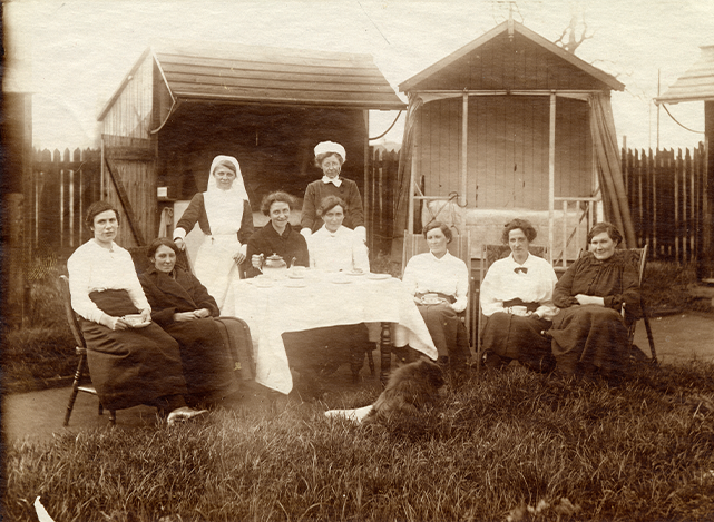 Nurses and patients sat outside open-air hospital huts in the 1910s
