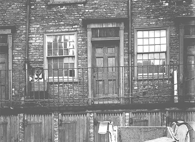 Terraced house in York slum area of Hungate with shared water-pump and shared toilets in the street below