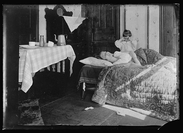 US woman sick with influenza in her home in 1918 with young child crying nearby
