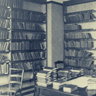 Interior of a library, featuring books on shelves, a desk stacked with books, and two wooden chairs.