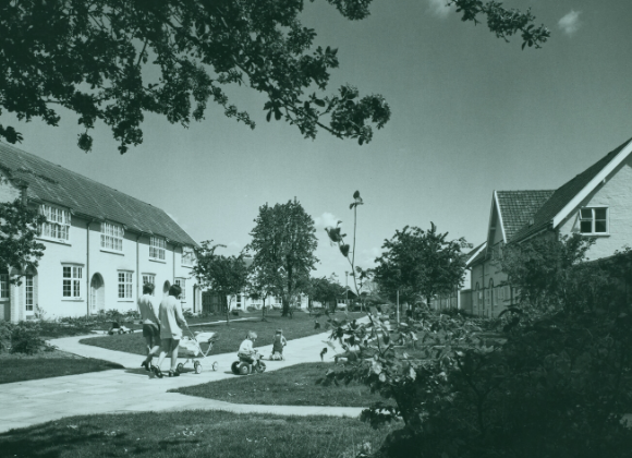 Black and white image of an urban housing development, white houses on left shaded by a tree in foreground. Women push prams and a small child plays on a bike. Date is 1960-1970.