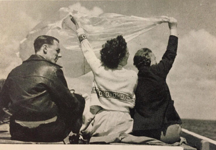 Image of a man and two women on a boat with their backs to the camera, the women blowing a white cloth which is blowing in the wind.