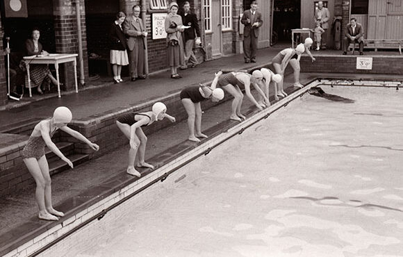 Girls lining up by the edge of a swimming pool in bathing suits and caps ready for a swimming race