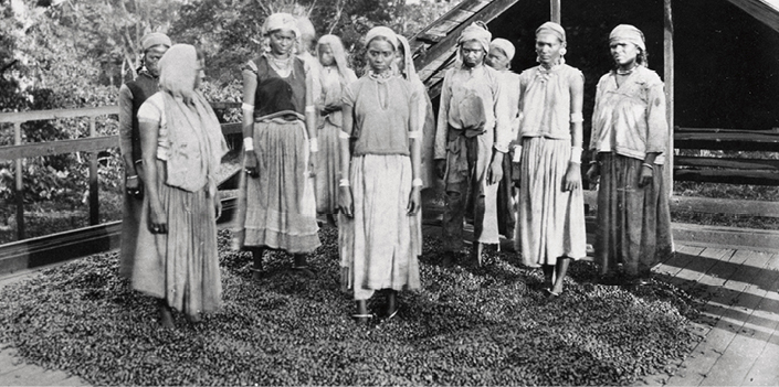 Black and white image of several women outside a cocoa shed standing on cocoa beans