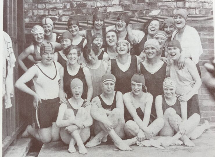 A black and white photo of a group of women in bathing costumes and caps smiling and laughing