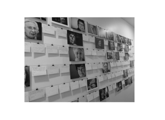 Black and white image of postcards with photographs of older people's faces mounted on a wall