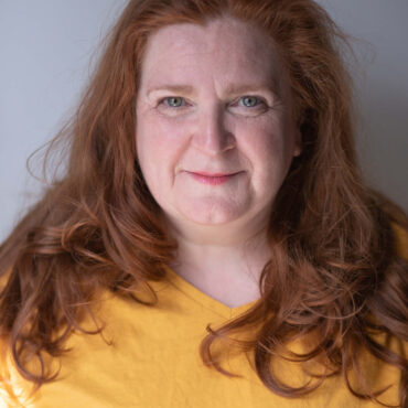Headshot of woman with long red hair wearing a yellow top in front of a grey background.