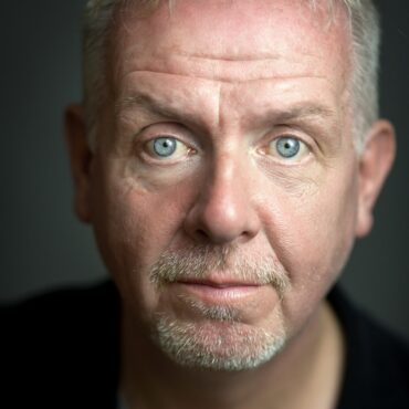 Headshot of man with light grey hair and a beard and light blue eyes wearing a dark top in front of a dark-grey background.
