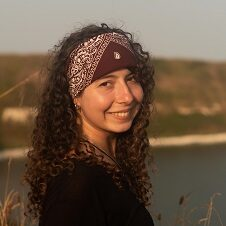 Young woman with long brown curly hair wearing a patterned bandana and smiling at the camera. A body of water and green hill are in the background.